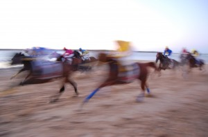 horses racing on a beach in a blurry photo capture